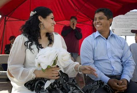 Pareja separada por una deportación se casó en la malla fronteriza