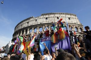 """Demonstrators make their way past the Colosseum during the Europride gay rights march in Rome, Saturday, June 11, 2011. The Europride parade, held every year in a different European city, ends Saturday evening in Circus Maximus, a grassy field where ancient Romans would gather for entertainment, where Lady Gaga is expected to sing """"Born This Way"""". Organizers hope the event will draw attention to discrimination homosexuals face in some parts of the world. (AP Photo/Andrew Medichini)"""