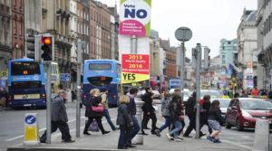 """D01 DUBLÍN (IRLANDA), 22/05/2015.- Varias personas caminan junto a dos carteles sobre el referéndum para la legalización del matrimonio entre parejas del mismo sexo en Dublín, Irlanda, hoy, 22 de mayo de 2015. Poco más de tres millones de ciudadanos irlandeses con derecho a voto están llamados hoy a las urnas para decidir si aceptan que un """"matrimonio puede ser contraído de acuerdo con la ley por dos personas sin distinción de su sexo"""". La República de Irlanda ratificó en julio de 2010 la ley de Relaciones Civiles que concedía reconocimiento legal a las parejas de hecho del mismo sexo. EFE/AIDAN CRAWLEY"""