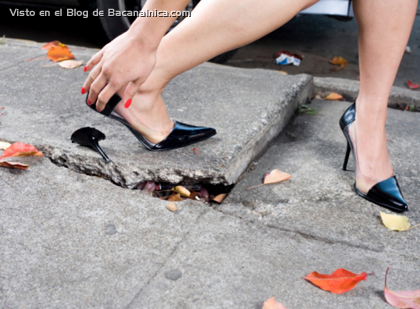 Young woman with broken shoe heel on sidewalk